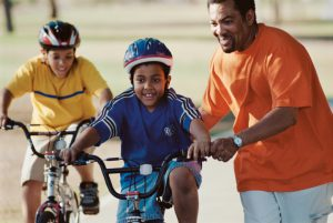 Father helping his son ride a bike (Photo by Thinkstock)