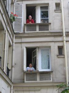 George Alter and his wife, Elyce Rotella, in the windows of their apartment in Paris. (Photo courtesy of George Alter)