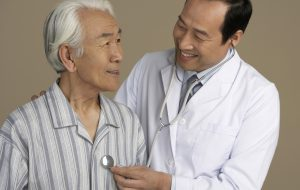 Chinese doctor listening to man's heart with stethoscope (Photo by Thinkstock)