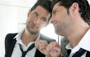 Handsome narcissistic suit proud young man looking himself in the mirror (Photo by Thinkstock)