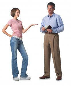 Young woman puts out her hand as her father pulls out his wallet to give her money (Image by Thinkstock)