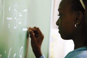 Girl writing math problem on chalkboard (Photo by Thinkstock)