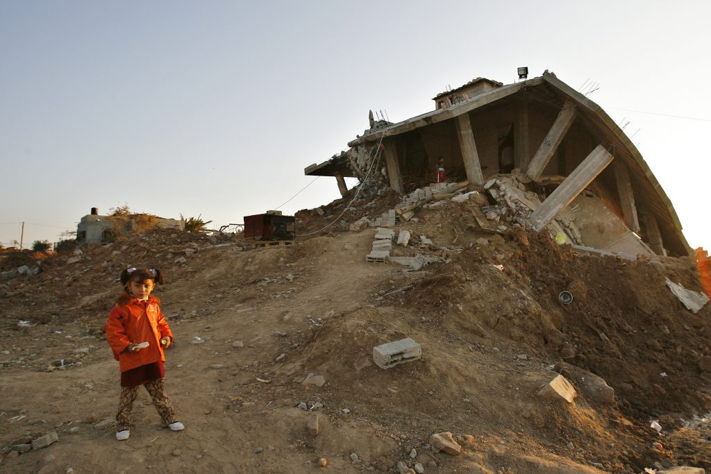 A Palestinian girl stands next to a home destroyed