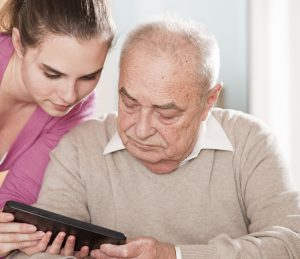 Young woman and senior man with tablet pc. Thinkstock.