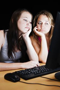 Two sad, bored young women look at their computer monitor