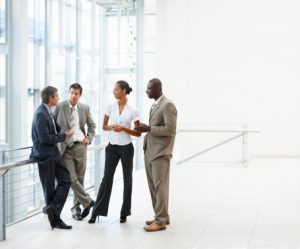 Image of four business people discussing at the hallway