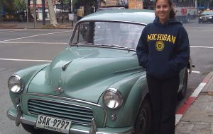 Tissyana Camacho standing next to a vintage car.