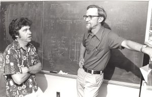 Kent Jennings and Phil Converse having a discussion in front of a blackboard