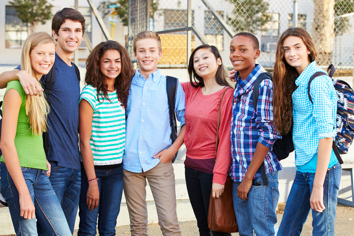 Group of teenagers outside classroom smiling at camera