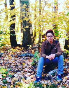 He, sitting on the ground in the forest