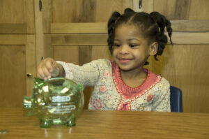 A student in the Head Start program in Pontiac learning about savings as part of the MI-SEED, or Saving for Education Entrepreneurship and Downpayment. Shanks was involved with the policy demonstration program in Michigan around child savings accounts from 2004 to 2009. Images courtesy: Trina Shanks